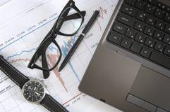 Laptop, glazen, horloge, en informatiegrafieken Stock Fotografie