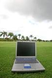 Laptop on a golf course. A photo of a computer set on the rough of a golf course Stock Photos