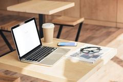 Laptop with google website, smartphone and business newspaper on table. In coffee shop stock photography