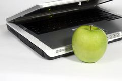 Laptop and green apple Stock Image