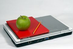 Laptop, green apple, book, and pencil Stock Images
