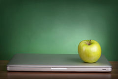 Laptop and green apple Stock Photography