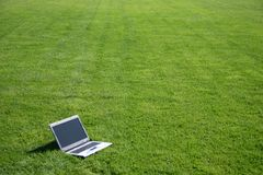 Laptop in a green field. Modern laptop in a clean green sports field Stock Photo