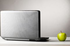 Laptop with green fresh apple royalty free stock images