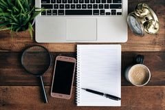 Laptop, green plant, clock, magnifying glass, phone, coffee and blank notebook on a wooden table Royalty Free Stock Photography