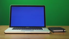Laptop with a green screen and black notepad on table. Green screen background. Dolly shot. Zoom in motion stock video