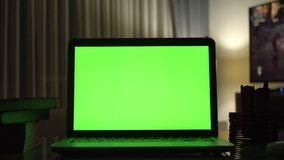 Laptop with green screen. Dark home office . stock video footage