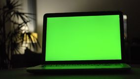 Laptop with green screen. Dark home office . stock footage