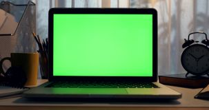 Laptop with green screen. Dark office. Dolly move right to left. Perfect to put your own image or video.Green screen of technology