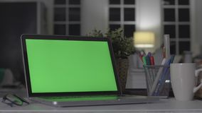 Laptop with green screen. Dark office. Perfect to put your own image or video. Green screen of technology being used. Chroma key laptop stock video footage