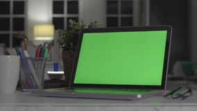 Laptop with green screen. Dark office. Perfect to put your own image or video. Green screen of technology being used. Chroma key laptop stock footage