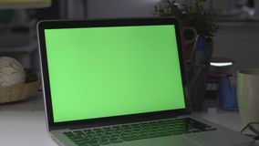 Laptop with green screen. Dark office. Perfect to put your own image or video. Green screen of technology being used. Chroma Key laptop stock video