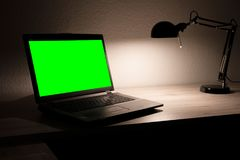 A Laptop with green screen on an empty desk Royalty Free Stock Photography