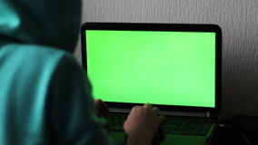 Laptop with a green screen. A girl hacker is typing something and trying to hack the system stock footage