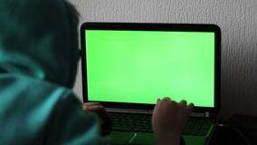 Laptop with a green screen. A girl hacker is typing something and trying to hack the system stock video footage
