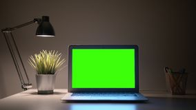 Laptop green screen. Green Screen Laptop display with a lamp on a wall background in Home Office stock photography