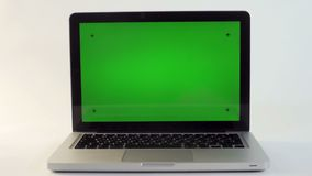 Laptop with a Green Screen. On a White Backdrop stock footage