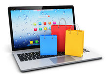 Laptop with group of color paper shopping bags Royalty Free Stock Image