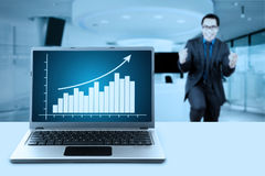 Laptop with growing chart and businessman Royalty Free Stock Photography