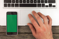 Laptop hand and phone. Laptop phone and typing hand on the wooden desk Stock Photo