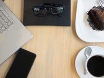 Laptop, Handy, Kaffeetasse, Schokoladenkuchen und Gläser an lizenzfreie stockfotos