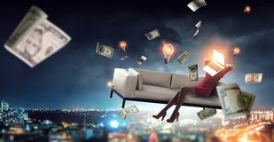 Laptop headed woman. Business efficiency concept. Laptop headed businesswoman in a red dress sitting on a sofa in the sky over city royalty free stock photo