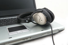 Laptop and headphone. Shot of laptop with headphone isolated over white royalty free stock photography