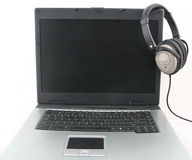 Laptop and headphone. Shot of laptop with headphone isolated over white royalty free stock photo