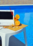 Laptop, headphones, cocktail near the swimming pool. Royalty Free Stock Photo