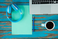 Laptop, headphones and coffee on wooden table Royalty Free Stock Images