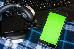Laptop and headphones smartphone with green screen for key chrom Royalty Free Stock Photo
