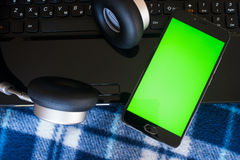 Laptop and headphones smartphone with green screen for key chrom Stock Photos