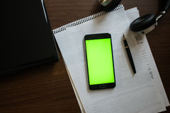 Laptop and headphones smartphone with green screen for key chroma screen. On the. Table with notebook and pen Royalty Free Stock Photos