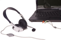 Laptop with headset Stock Images