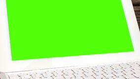 Laptop on his desk. Green screen for your custom screen content.  stock footage
