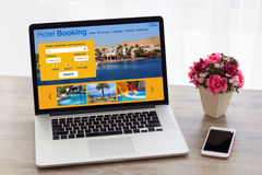Laptop with hotel booking screen on table near phone flower Stock Image