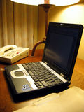 Laptop on Hotel Room Desk. This is a close up image of a laptop computer on a hotel room desk with a telephone royalty free stock image