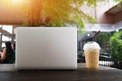 Laptop i filiżanka na drewnianym stole, laptop z pustym ekranem na stole Sklep Z Kawą Zamazany tło pojęcia prowadzenia domu posia Zdjęcia Royalty Free