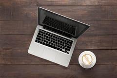 Laptop i filiżanka kawy na drewnianym tle Zdjęcia Royalty Free