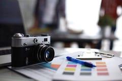 Laptop i kamera na biurku, dwa biznesmena stoi w tle fotografia royalty free