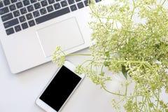 Laptop i mądrze telefon z kwiatem na biurku z kopii przestrzenią fotografia royalty free