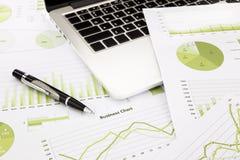 Laptop i pióro z zielonymi biznesowymi mapami, wykresy, informacja a Zdjęcia Stock