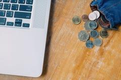 Laptop i wiele pieniądze monety w błękitnej torbie na drewno stole fotografia stock