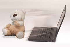Laptop and injured toy bear Stock Photography