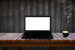 Laptop with isolated screen on wooden table and a cup of coffee. Royalty Free Stock Photos