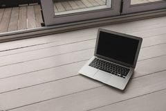 Laptop kept on a wooden surface. High angle view of laptop kept on a wooden surface at home stock photography