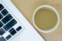 Laptop keyboard with coffee paper cup on wood desk Royalty Free Stock Photography