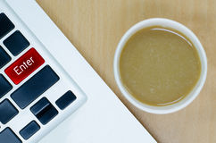 Laptop keyboard with coffee paper cup on wooden desk, enter key Stock Image