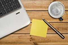Laptop keyboard, empty yellow adhesive paper, pen and coffee cup on desk background.  stock photos