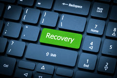 Laptop keyboard. The focus on the Recovery key. Close-up laptop keyboard. The focus on the Recovery key. Toning is blue Stock Photos